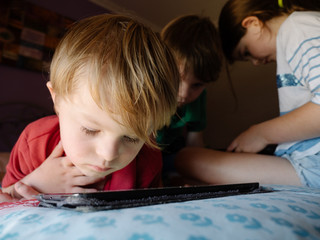 Preschool Boy Using Tablet with Brother and Sister in Background