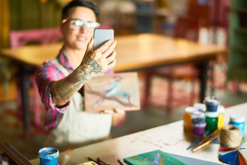 Portrait of modern creative woman taking selfie with her artwork  in art studio, focus oh tattoed hand holding smartphone, copy space