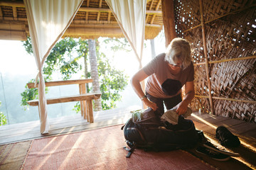 Mature woman packing up travel bags in morning light