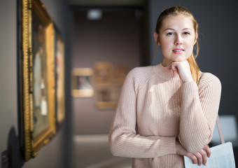 Portrait of joyful woman looking at pictures