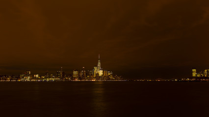 Panorama of Manhattan across Hudson River at night, New York City. Brightly lit New York skyscrapers during winter holiday season.