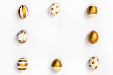 Top view of easter eggs colored with golden paint in differen patterns arranged in square. Various...