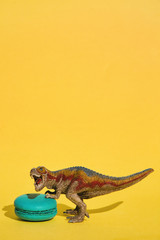 Small T-Rex defending sweet macaroon