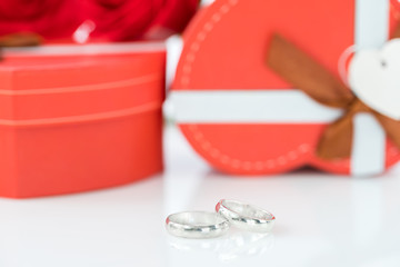 Wedding ring and heart-shaped box on white