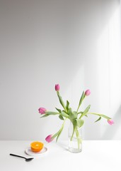 Tulips on table with orange and white background