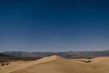Desert sand dunes at night with stars
