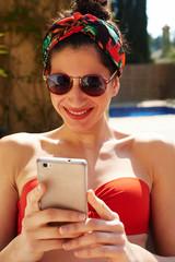 Slim girl in red bikini smiling using mobile phone.