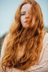 A young woman with ginger hair and freckles with her hair blowing over her face on a wintery day
