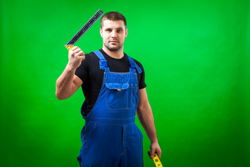 A dark-haired male construction worker in a black T-shirt and blue construction overall holds construction r L shape angle square ruler  and  rare  magnetic  level   on a green isolated background