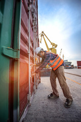 container inspector in surveying the condition of container before delivery unit shipment to the carrier ship in port or customers