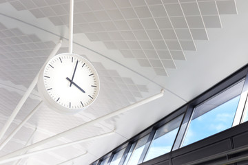 white clock hang on the floor between departure and arrival hall, terminal of international airport