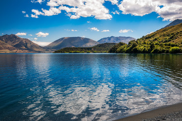 Beautiful View of Lake Wakatipu with clouds reflections in the water at Wilson Bay, Otago Region, New Zealand, Southern Island.