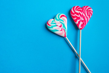 Close up and top view of colorful heart shaped striped lollipops isolated on blue background with copy space, love or Valentine's day concept