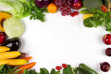 Flat lay of vegetable and fruits with empty space of white background on middle, Top view. Vegetarian, diet food, grocery fresh produce and healthy eating concept.