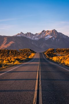 A road in Eastern Sierra leading up to a beautiful snow coverred mountain with morning light