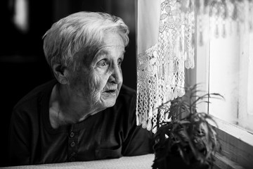 Elderly woman looking sad out the window.