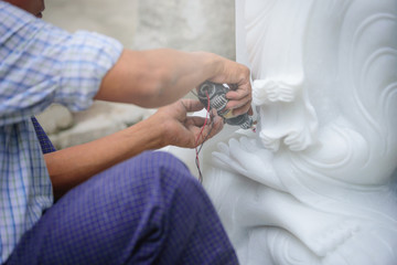 Close-up carvers using electric drill on a marble to carve a statue Buddha in Mandalay, Myanmar.
