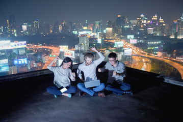 Group of business people working on a rooftop at night with blurry city background, business technology concept