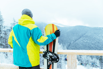man stands with snowboard on the top of the hill