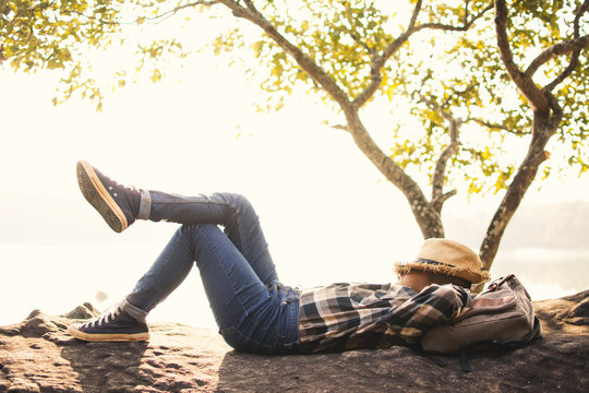 Boy backpacker sleeping on the rock in nature , Relax time on holiday concept travel,selective and soft focus,tone of hipster style
