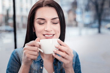 Time to enjoy. Pretty brunette keeping smile on her face and closing eyes while drinking warm liquid