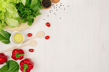 Border of fresh green greens, red paprika, cherry tomato, pepper, oil and utensils on soft white wooden background.