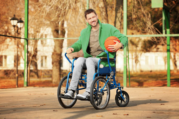 Young man in wheelchair with ball on playground