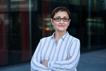 Older business woman headshot. Close-up portrait of executive, teacher, principal, CEO. Confident and successful middle aged woman 40 50 years old wearing glasses and shirt.