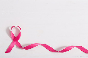 healthcare and medicine concept. pink breast cancer awareness ribbon on wooden white background
