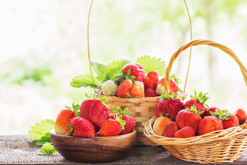 strawberries in baskets on wooden table outdoor