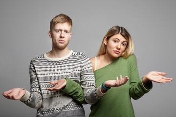 Picture of funny young couple man and woman having doubtful clueless looks, shrugging shoulders with open palms, feeling lost, looking at camera in confusion and uncertainty. Body language