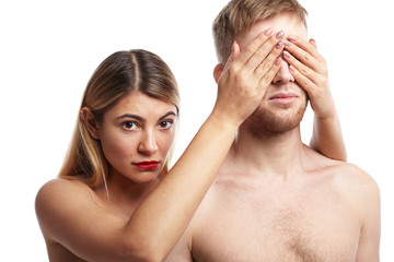 Isolated picture of two lovers posing naked in studio: attractive blonde woman with tanned smooth skin and facial piercing covering eyes of her bearded boyfriend and staring at camera with shy look