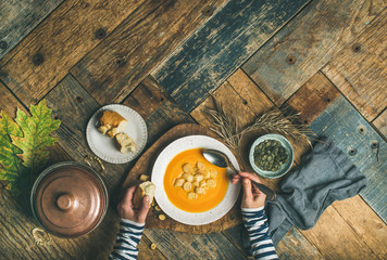 Flat-lay of female hands and Fall warming pumpkin cream soup with croutons and seeds over rustic wooden table background, top view. Autumn vegetarian, vegan, healthy comfort food eating concept
