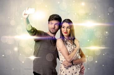 Smiling couple taking selfie in glitter light