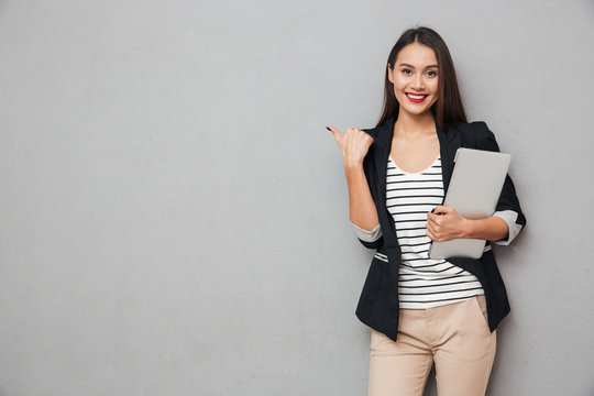 Smiling asian business woman holding laptop computer and pointing away