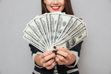 Cropped image of smiling business woman showing money at camera