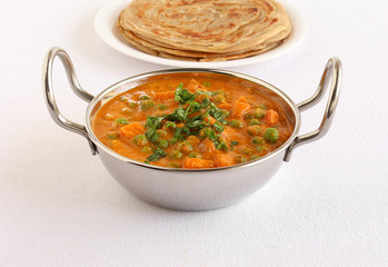 Indian vegetarian side dish, peas and carrot curry cooked in tomato puree, in a wok and in the background is a stack of Kerala parathas.