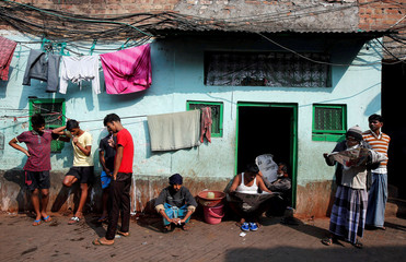 People brush their teeth as others read newspapers on a winter morning in Kolkata