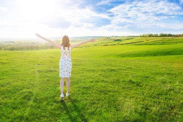 Young woman enjoying nature and sunlight in green spring or summer field