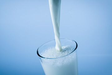 Pouring milk into a glass, splash on blue background