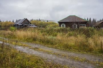 Rural road in the background of ancient village houses, late autumn. Very ancient, forgotten village in the Siberian taiga.
