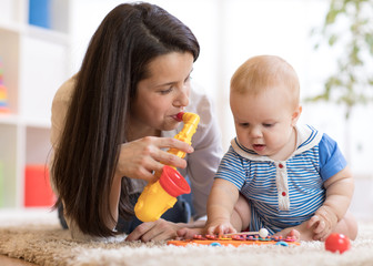 cute mother and baby boy play together indoors at home