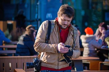 A tourist man with a camera came to another city looking into the phone looking for something in his smartphone. A man near the cafe expects friends