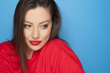 beautiful woman in a red blouse on a blue background