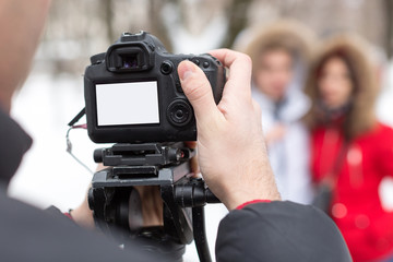 season, hobby, art work concept. close up of professional camera with blank screen in the arm of photographer on the background of two models that wear winter clothes