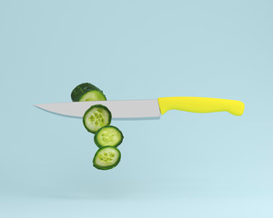 Cucumber cut into pieces with stainless kitchen knives on blue pastel background. minimal food idea concept. An idea creative to produce work within an advertising marketing communications or artwork.