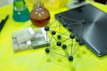 chemical composition, science, study concept. on the table in chemical class there are different multicolored glass vessels, black laptop for creating projects and model of molecule of square form