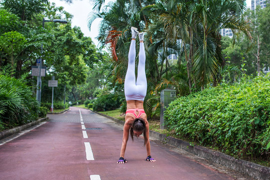 Rear view of fitness woman doing handstand exercise standing straight on outstretched arms park lane in summer
