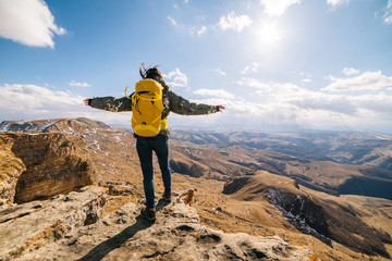 active young girl travels through the Caucasian mountains with a yellow backpack, enjoys the sun and nature