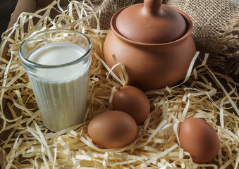 Clay jugs, eggs, glass of milk, on the straw and a burlap.